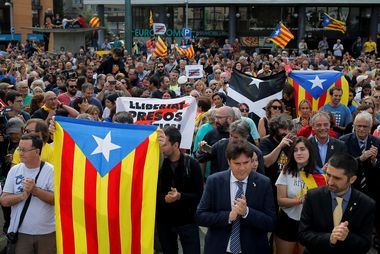 People hold up Catalan separatist flags during ceremonies marking the first anniversary of Catalonia's banned independence referendum in Girona, Spain, October 1, 2018. REUTERS/Jon Nazca