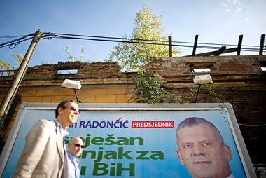 Bosnian men walk past election posters in Sarajevo, October 8, 2014. Bosnia's 3.3 million voters will choose a new political elite across six layers of government on Sunday in an election that, had it happened a few months ago, might have been a catalyst for change. Picture taken October 8, 2014. To match Preview BOSNIA-ELECTION/ REUTERS/Dado Ruvic (BOSNIA AND HERZEGOVINA - Tags: POLITICS ELECTIONS) - GM1EAA919FV01