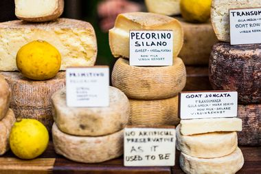 An appetising selection of continental cheeses on sale at Borough Market in London, UK. Horizontal colour image.