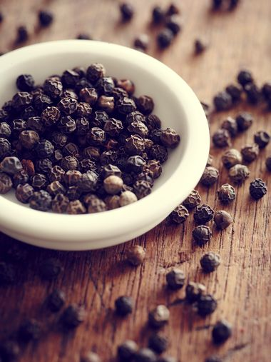 Black peppercorns in a white bowl and scattered on a wooden surface.