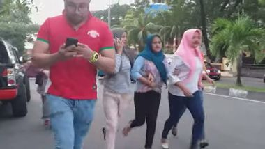 A man checks his phone as people run after an earthquake in Ternate, North Maluku, Indonesia July 14, 2019 in this still image taken from social media video. Egon Enviro Batu Bacan via REUTERS ATTENTION EDITORS - THIS IMAGE HAS BEEN SUPPLIED BY A THIRD PARTY. MANDATORY CREDIT. NO RESALES. NO ARCHIVES