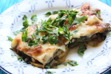 View of vegetarian lasagna with freshly chopped herbs on a white and blue plate by sunlihgt effect.
