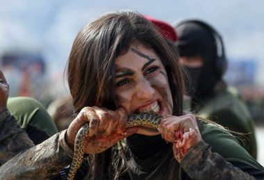 An Iraqi Kurdish Peshmerga female officer bites a snake while demonstrating skills during a graduation ceremony in the Kurdish town of Soran, about 100 kilometres northeast of the capital of Iraq's autonomous Kurdish region Arbil, on February 12, 2020. (Photo by SAFIN HAMED / AFP)