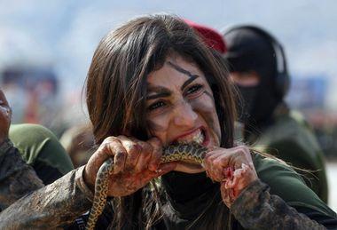 An Iraqi Kurdish Peshmerga female officer bites a snake while demonstrating skills during a graduation ceremony in the Kurdish town of Soran, about 100 kilometres northeast of the capital of Iraq's autonomous Kurdish region Arbil, on February 12, 2020. (Photo by SAFIN HAMED / AFP)