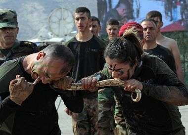 Iraqi Kurdish Peshmerga officers bite a snake while demonstrating skills during a graduation ceremony in the Kurdish town of Soran, about 100 kilometres northeast of the capital of Iraq's autonomous Kurdish region Arbil, on February 12, 2020. (Photo by SAFIN HAMED / AFP)