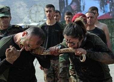 Iraqi Kurdish Peshmerga officers bite a snake while demonstrating skills during a graduation ceremony in the Kurdish town of Soran, about 100 kilometres northeast of the capital of Iraq's autonomous Kurdish region Arbil, on February 12, 2020. (Photo by SAFIN HAMED / AFP)