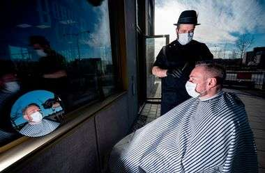 Hairdresser Abed Khankan cuts the hair of a customer outdoors as a precaution amid the novel coronavirus pandemic on April 17, 2020 in Malmo, Sweden. (Photo by Johan NILSSON / TT News Agency / AFP) / Sweden OUT