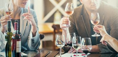 Group of unrecognizable caucasian adults tasting and evaluating different wines. Writing down the characteristics. Appearance, aroma and bouquet, taste and texture, aftertaste, and overall impression. There are two women and a man, backlit.